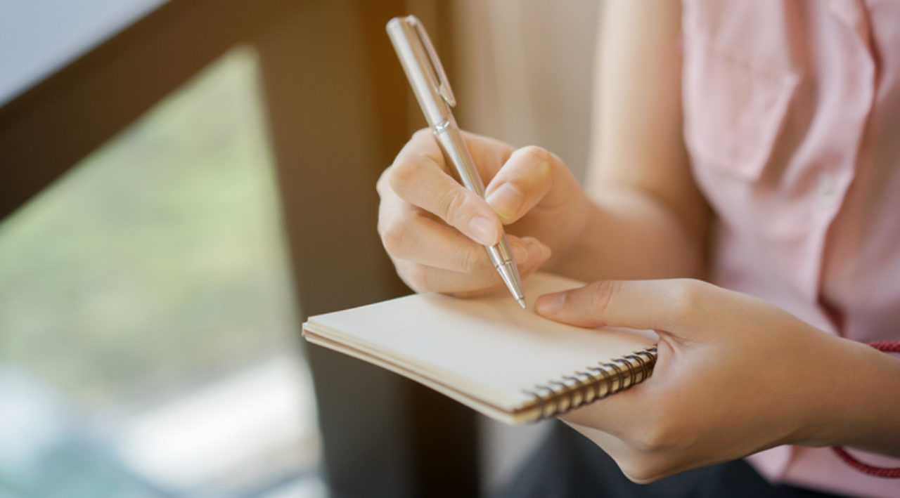 Closeup of woman's hands writing on a notepad