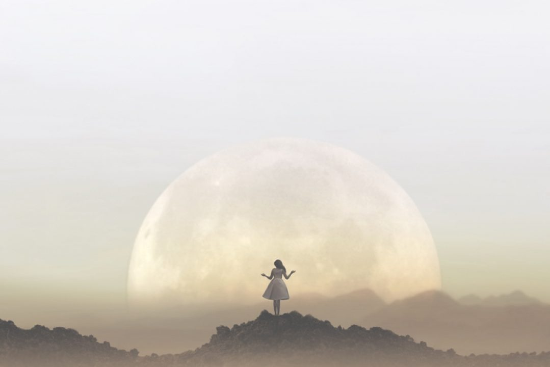 Silhouette of a woman meditating in front of a full moon.