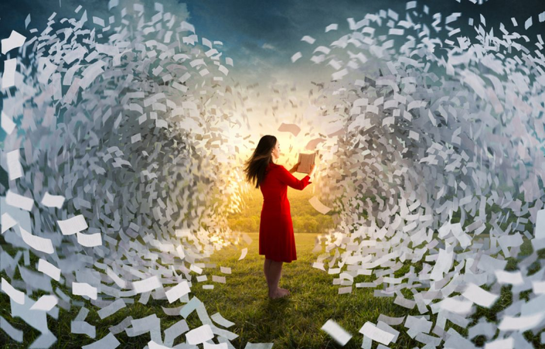 Woman reading a book surrounded by pages flying through the air