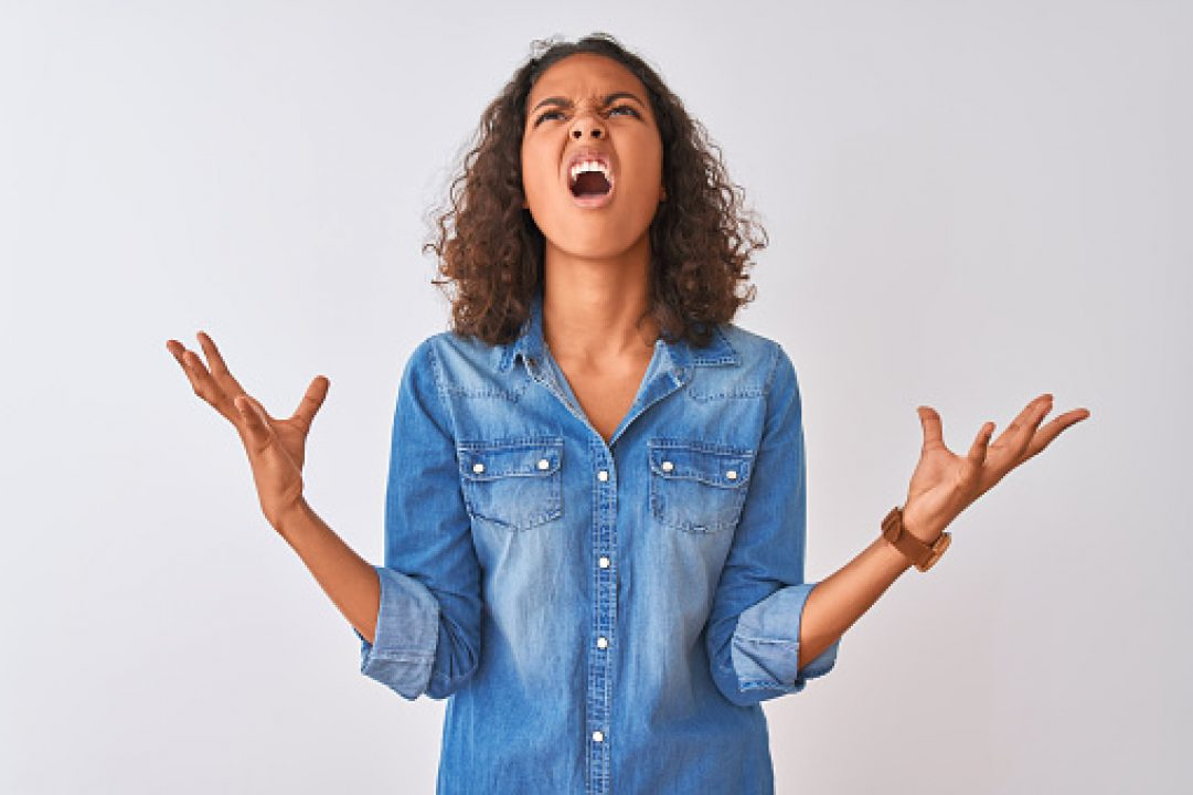 Woman looking up and throwing her arms in the air in anger and frustration