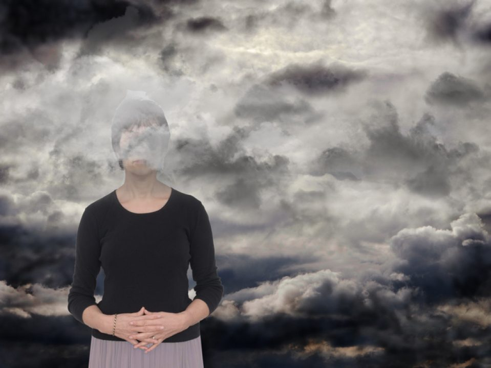 Sad woman with her head in dark clouds.