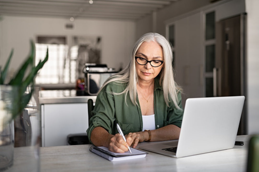 Senior woman taking notes in notebook while using laptop at home