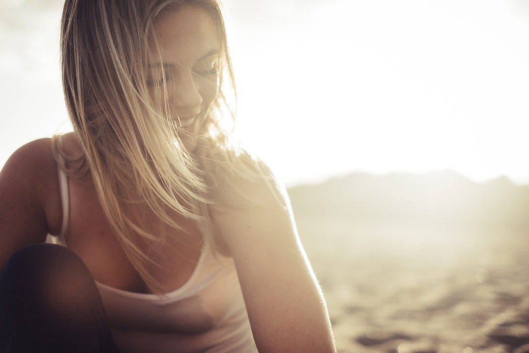 A young woman smiles, the sun behind her