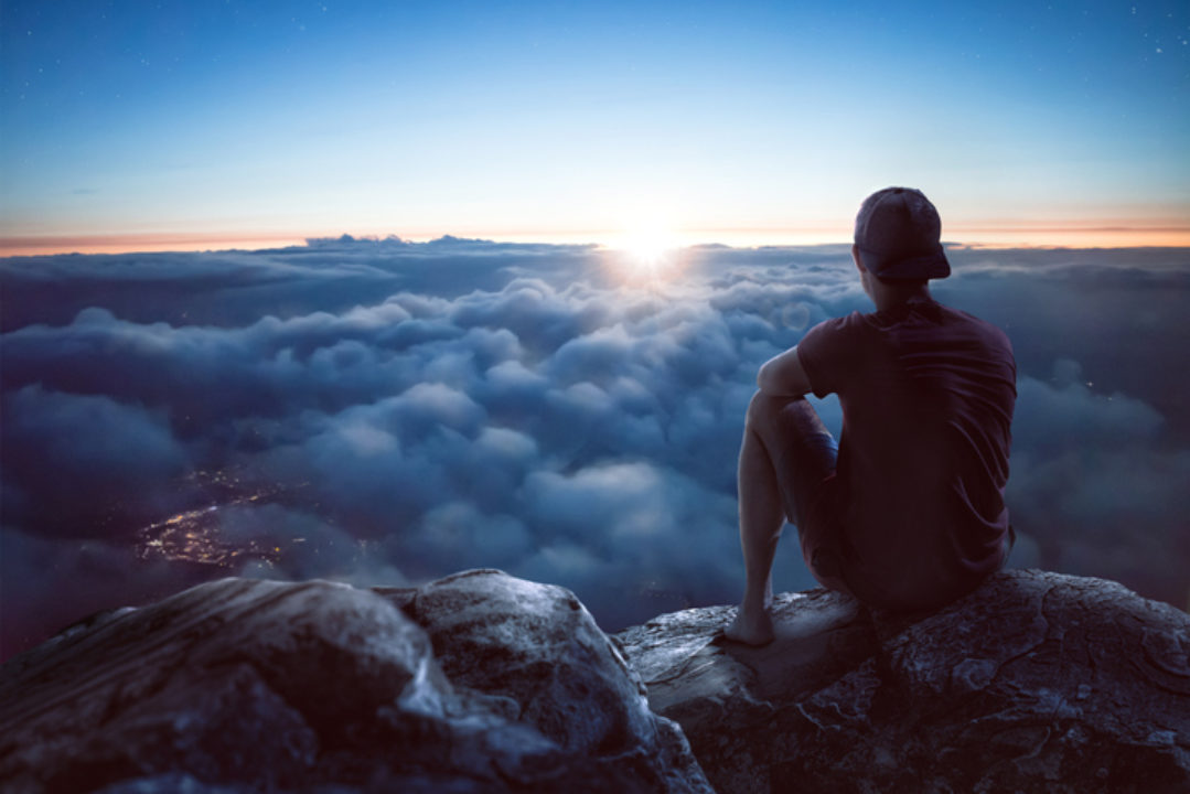 young man with view over clouds in contemplation of limiting beliefs