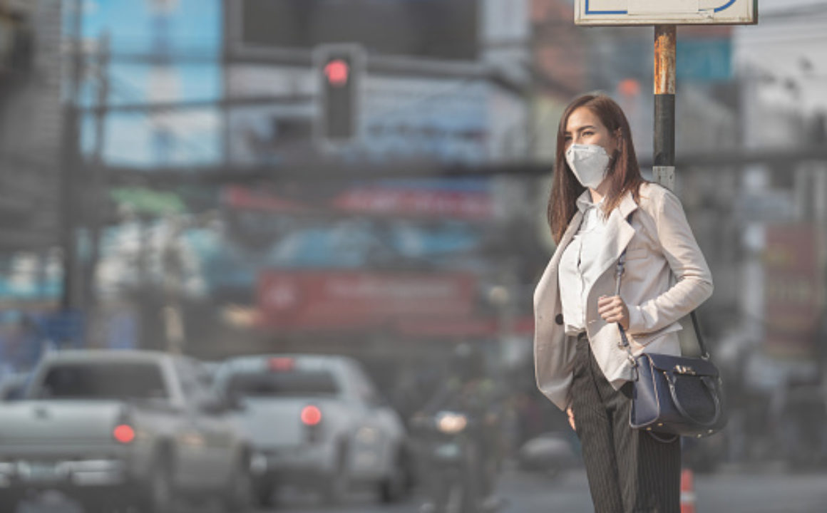 Woman dressed in business attire wearing air mask as she waits to cross the street