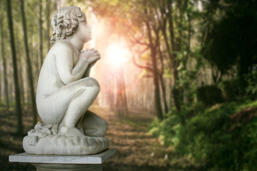 Cherub statue in forest with sun