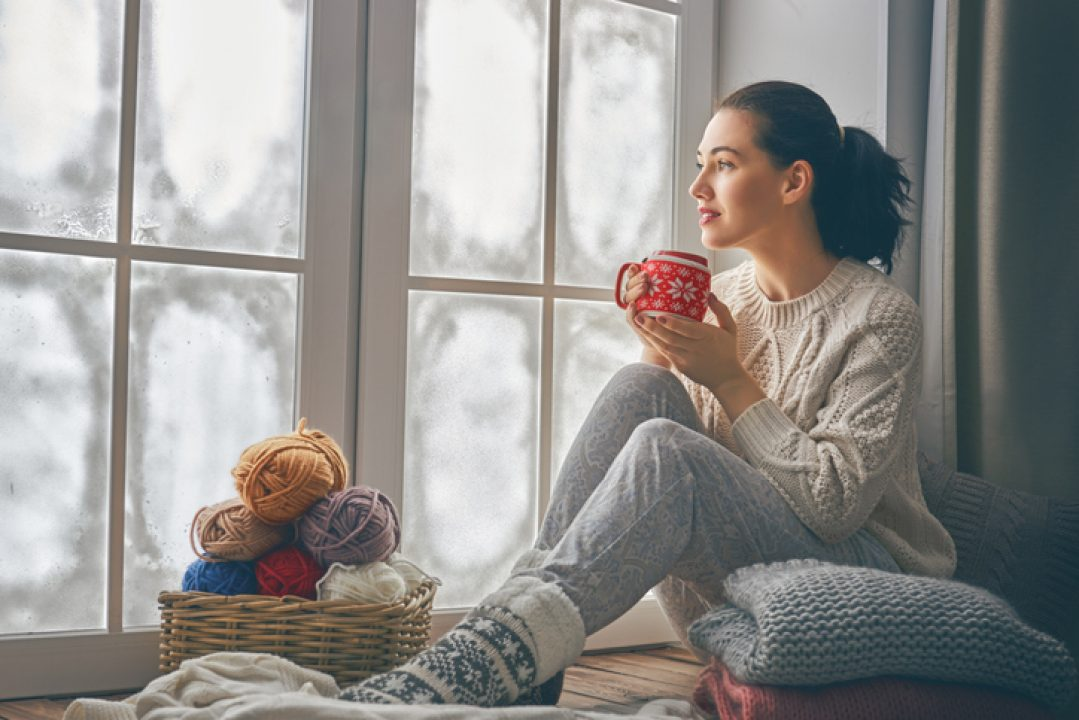Woman sitting in silence drinking coffee by window in contemplation during holiday season