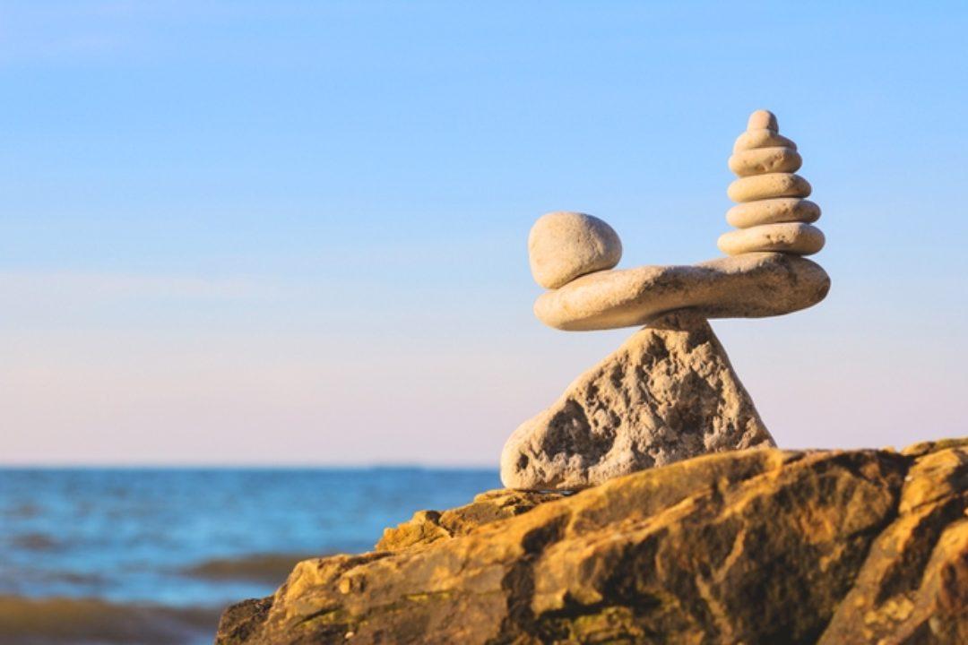 Zen stones balancing on ocean cliff