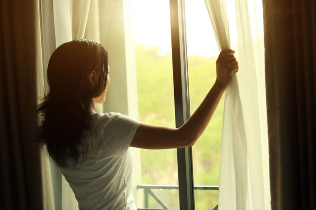 Woman looking out curtain