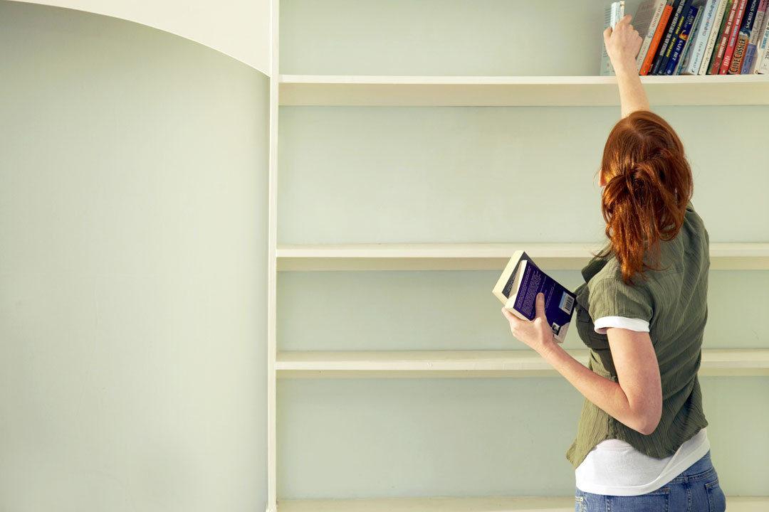 Woman putting things on shelf