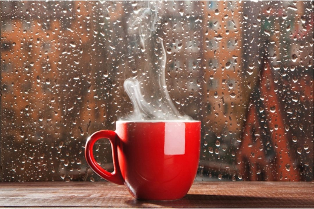 steaming coffee in rain covered window