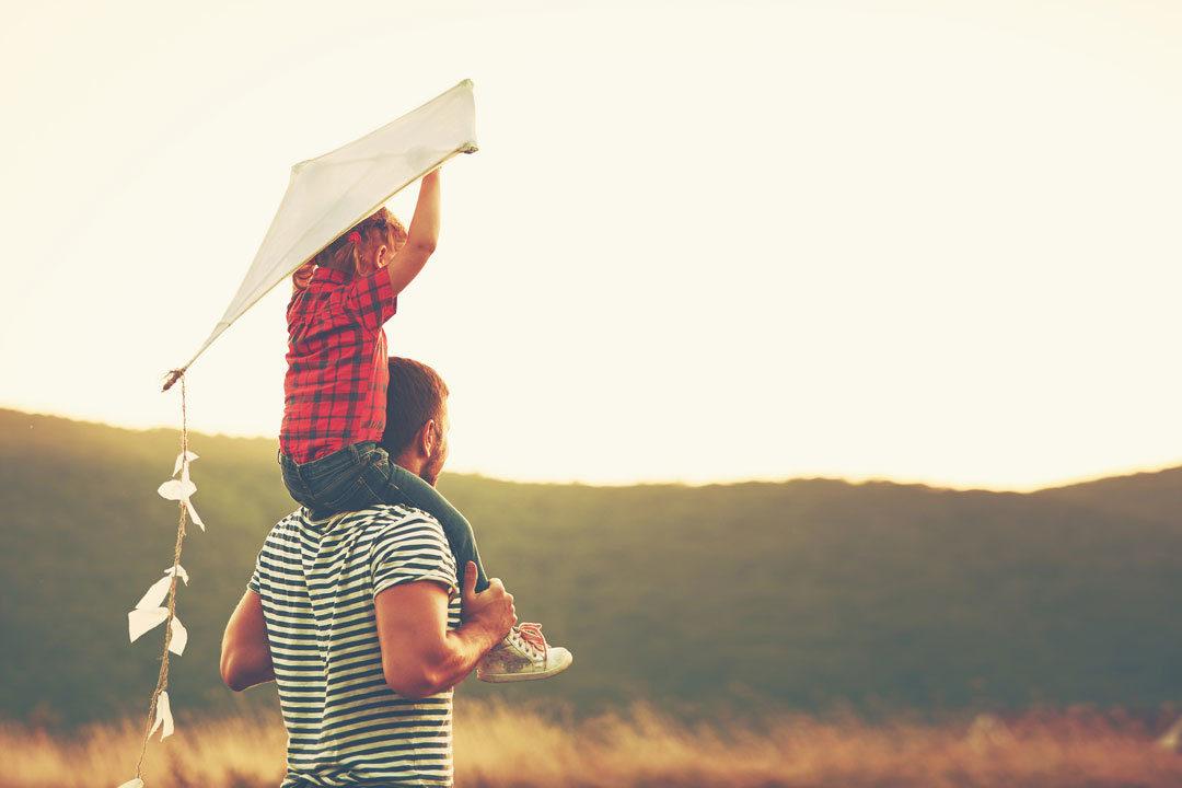 Dad holding child on shoulders