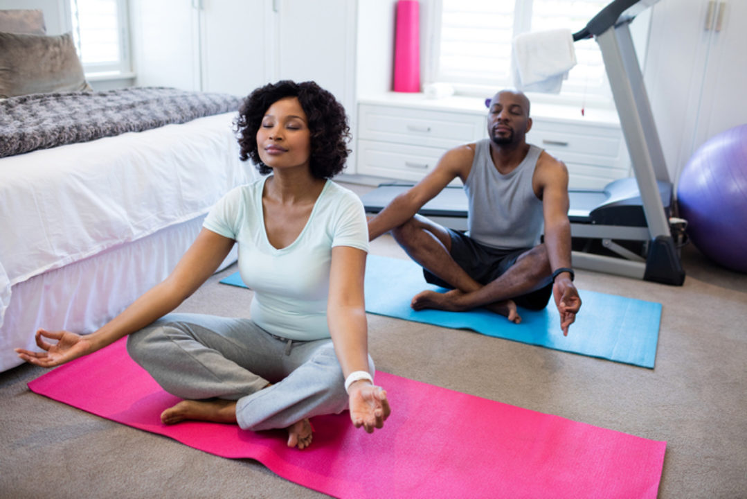 African American couple doing yoga together