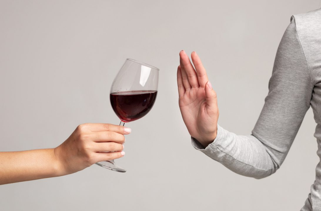 Woman rejecting wine glass for dry january