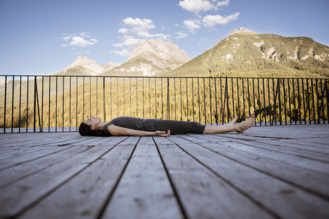 Elena Mironov laying in corpse pose during yoga nidra meditaton