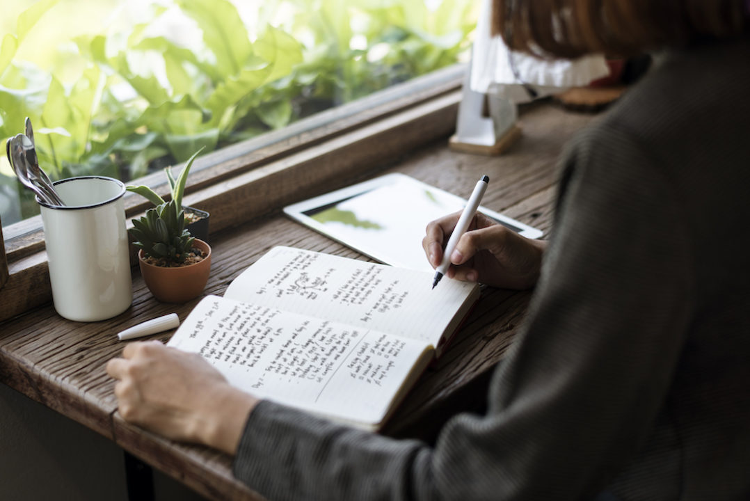 A lady writes upon her wooden desk