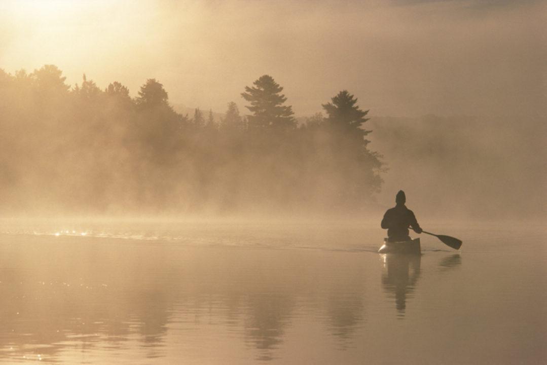 kayaking through fog and light on a lake
