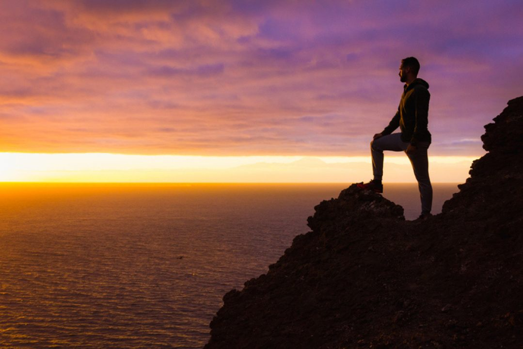 Visionary man standing on top of cliff edge staring at colorful sunset by the sea in Gran Canaria
