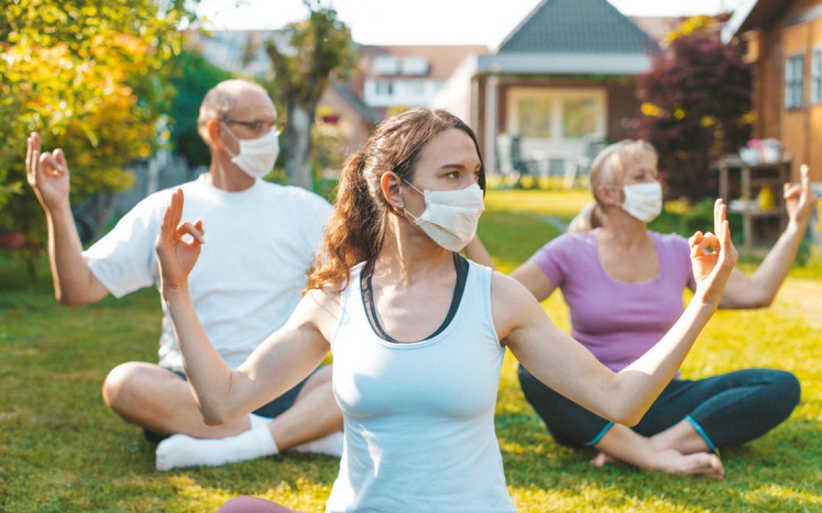 masked retreat goers do yoga