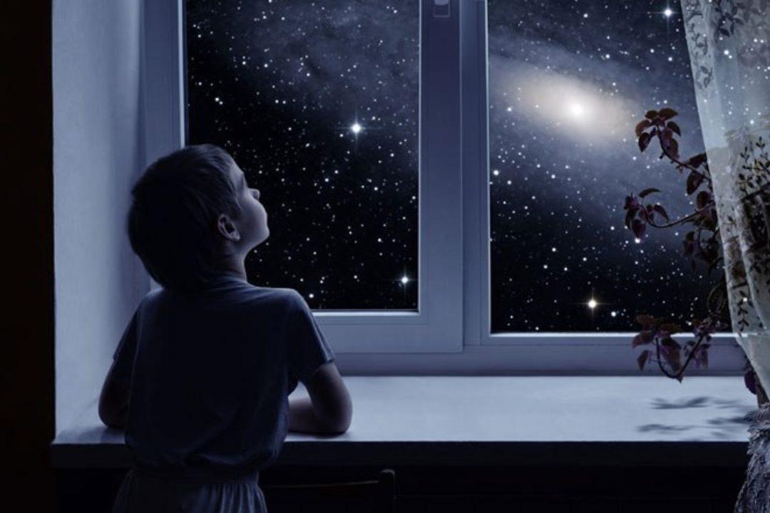 Child looking out dark window