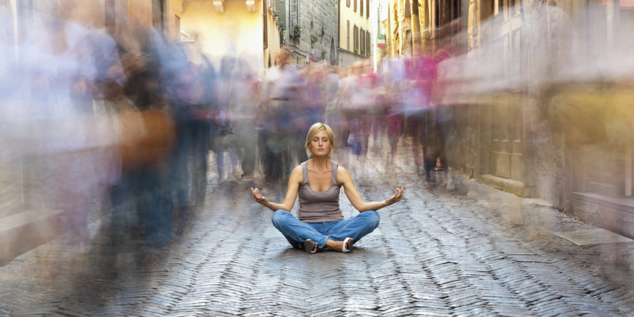 Woman meditates on busy sidewalk