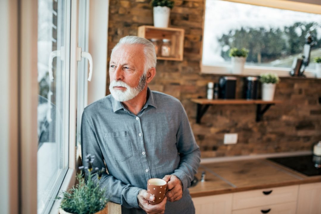Older man fighting pandemic fatigue, standing in the kitchen and looking through window, holding cup.