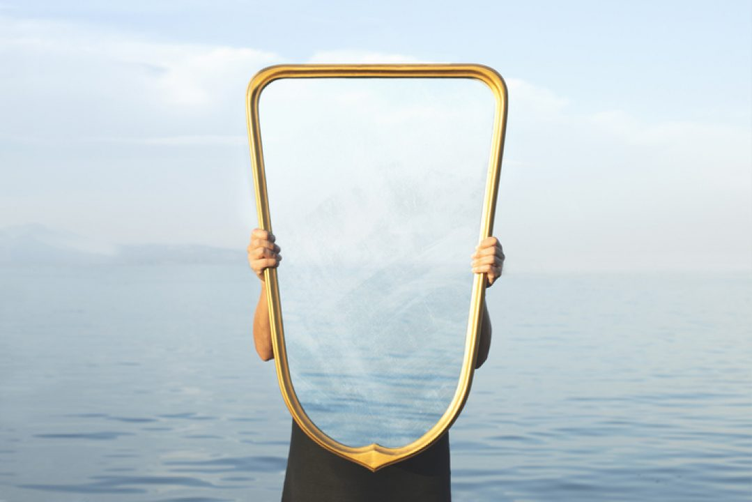 person holding mirror reflecting water