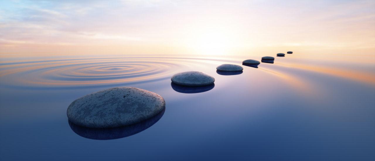Pebbles in wild calm ocean to show spiritual enlightenment