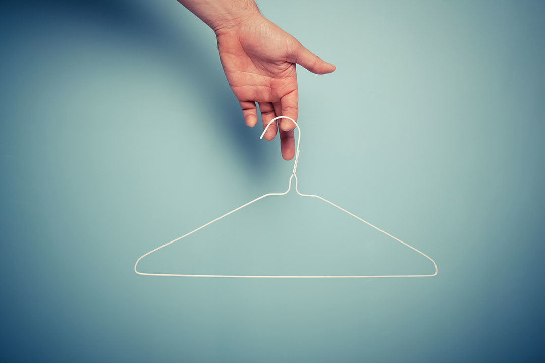 Person holding clothes hanger