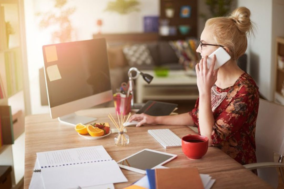 Woman at desk, on phone looking at computer
