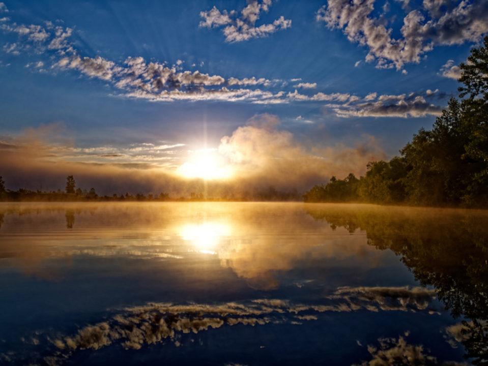 a sun rises over a lake giving a sense of hope