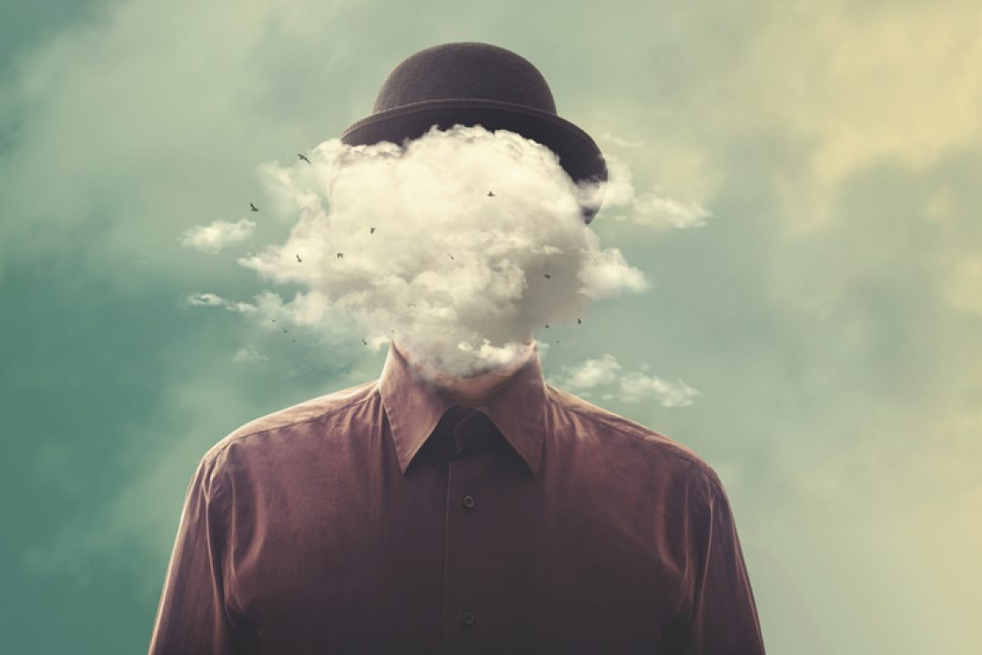 Surreal man with bowler hat with face hidden in clouds