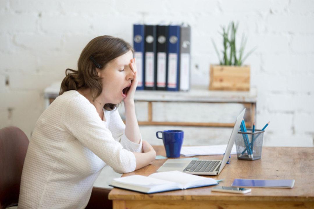 woman yawning at desk