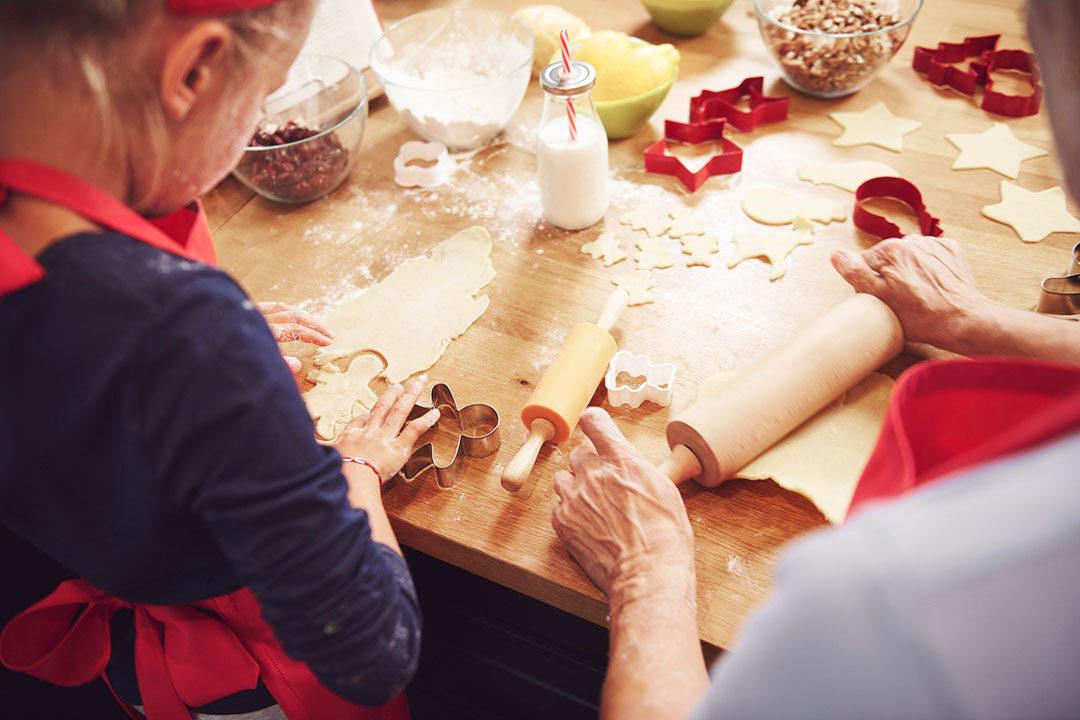 Grandma making cookies with granddaughter