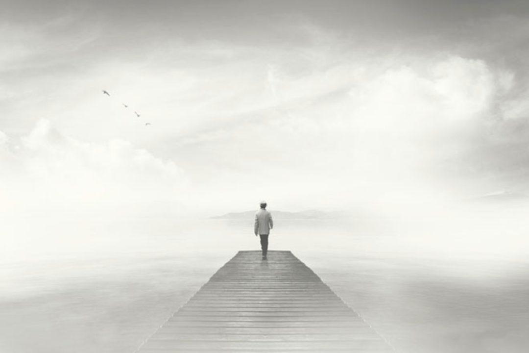 Man standing on foggy dock