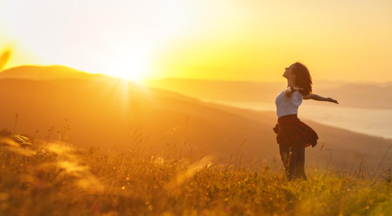 woman stretching into sunshine