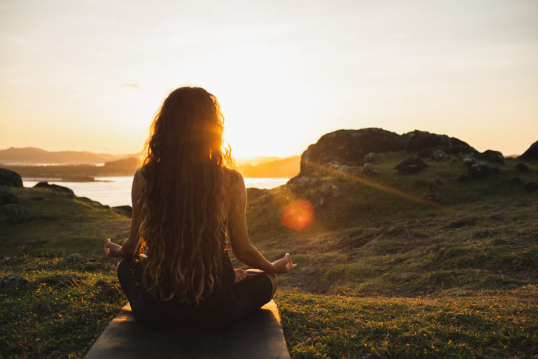 Woman meditating alone at sunrise in the mountains