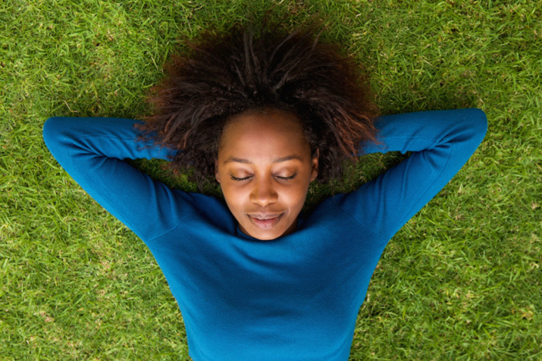 Black woman enjoying a guided meditation on a patch of green grass, feeling soothed and uplifted