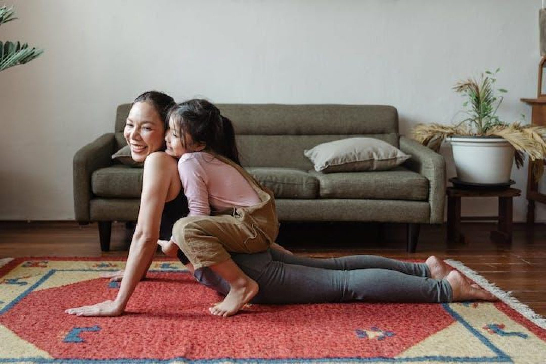 Mother doing yoga with daughter on back yoga for caregivers