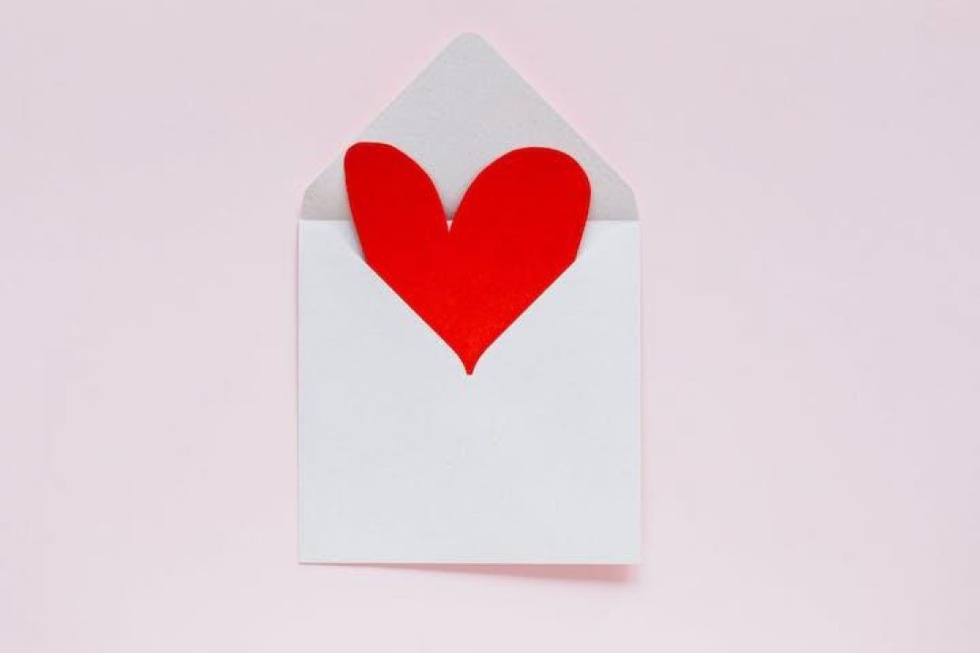 red heart-shaped paper coming out of envelope on pink background