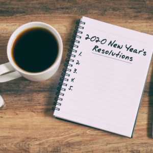 2020 New Year's Resolutions text on notepad next to coffee, smartphone, and pen