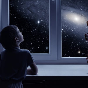 A little boy is standing near the window and looking outside at stars