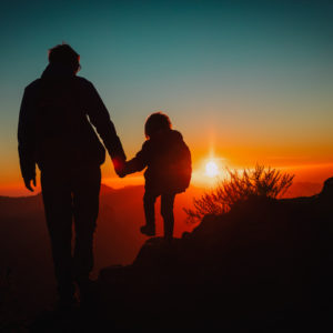 Father and daughter walking together at sunset