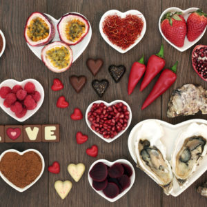 Aphrodisiac foods in heart-shaped bowls and loose on oak wood background