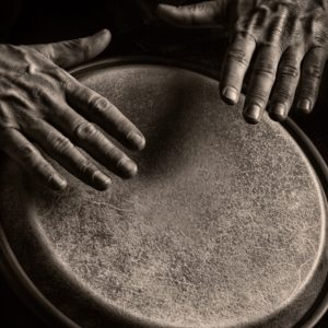 Man's hands playing drums