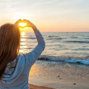 Girl with heart hand sign at sunset