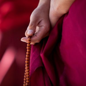 Monk holding mala beads