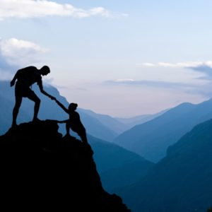 Person helps another climb mountain