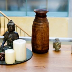 Buddha statue with candles on shelf