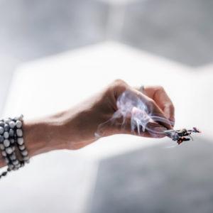 Woman's hand burning herbs